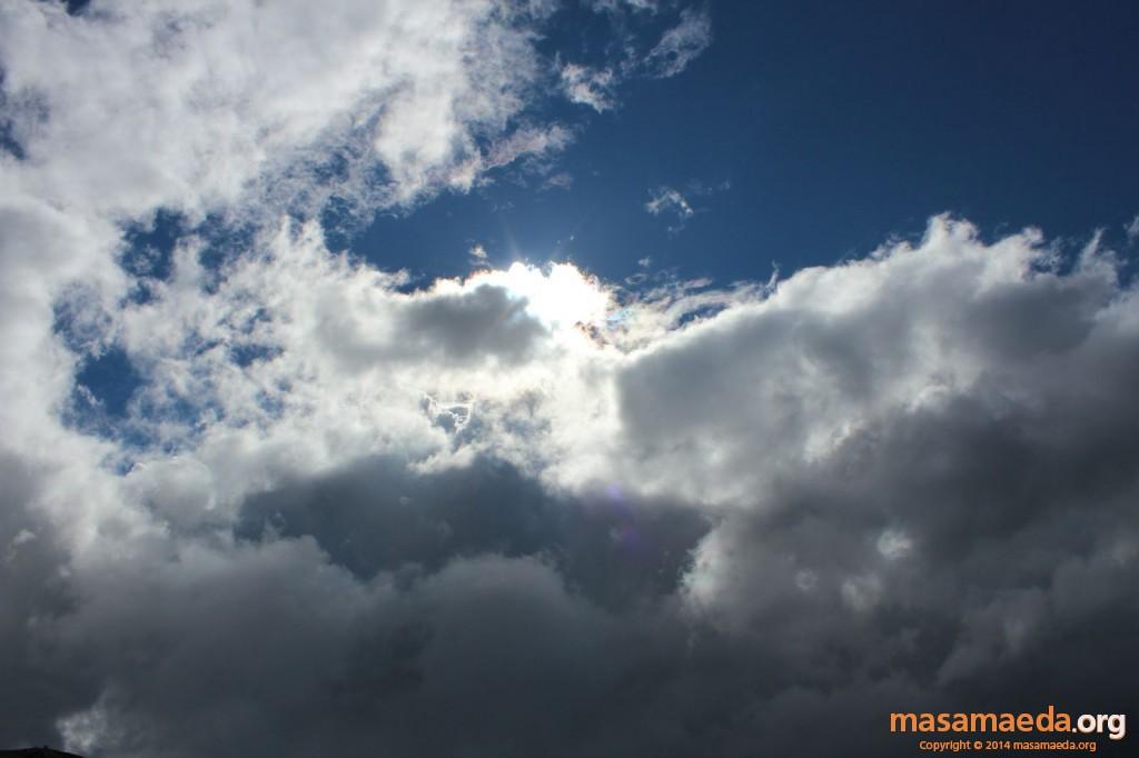虹色に光る太陽を覆い隠す雲